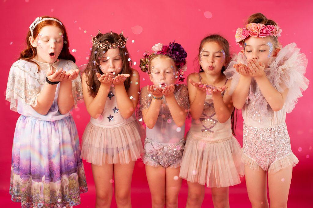 Girls blowing glitter confetti
