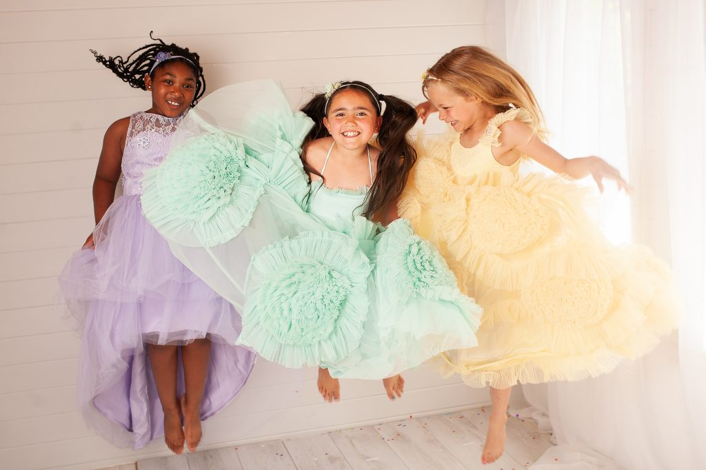 Young girls wearing colourful party dresses and jumping