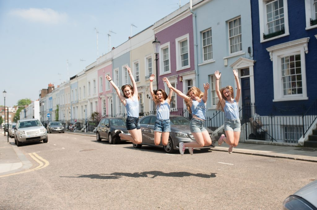 Teenagers jumping in the air in front of colourful terraced houses
